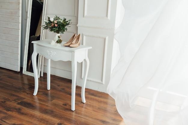 Bruids boeket van peones met witte schoenen