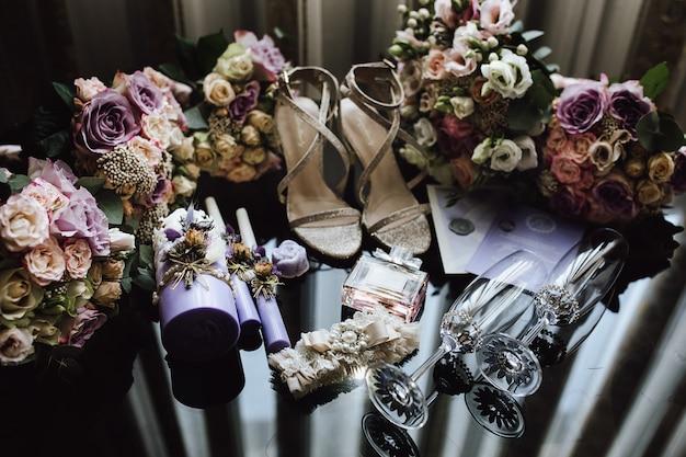 Bruids bruidsaccessoires in roze en paarse kleuren, ceremoniële champagneglazen, bruidsboeketten voor bruid en bruidsmeisjes