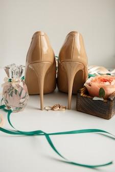 Bruids schoenen op hoge hakken in de buurt van parfumfles, trouwringen en verse bloemen
