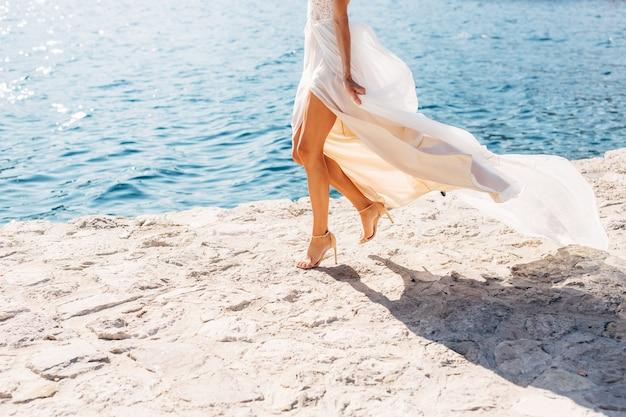 Bruidsbenen in sandalen met hoge hakken en met een wapperende rok loopt de bruid langs de pier