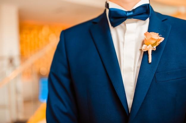Bruidsboeket een corsages op een pak van de bruidegom vlinderdas en corsages op een blauw pak