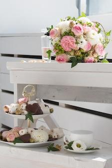 Bruidsboeket, fles parfum, kopje thee en etagère met snoep