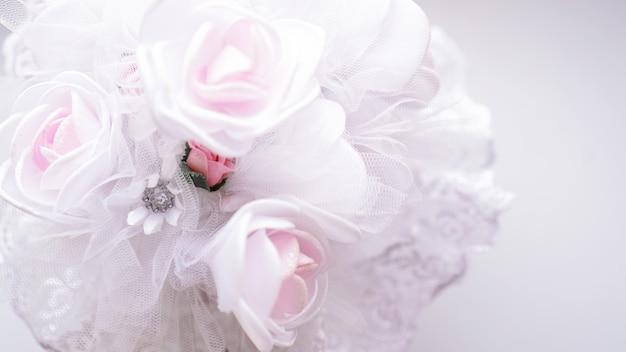 Bruidsboeket gemaakt van witte rozen op een wazige witte achtergrond