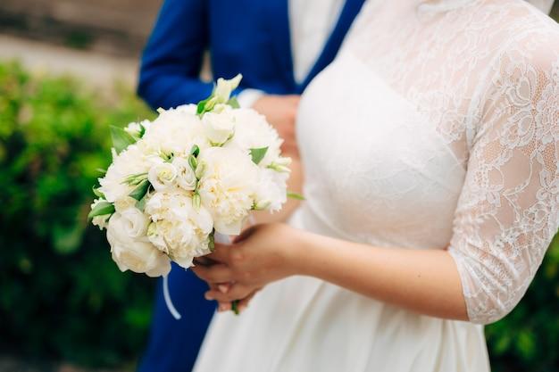 Bruidsboeket in de handen van de bruid tijdens de ceremonie