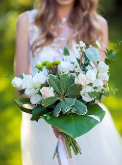 Bruidsboeket in de handen van een jong meisje