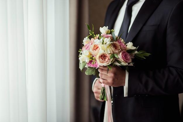 Bruidsboeket in handen, huwelijksboeket in handen van de bruidegom, bruidegomochtend, zakenman, huwelijk, man mode, man stijl