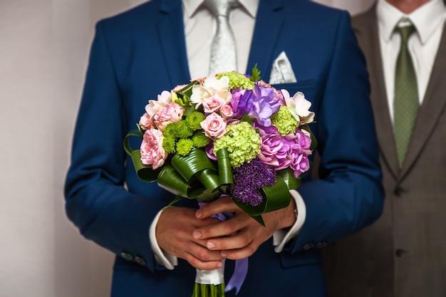 Bruidsboeket in handen van de bruidegom