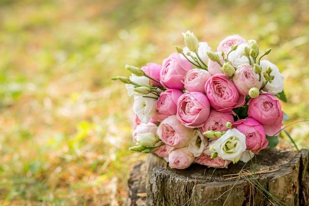 Bruidsboeket in rustieke stijl ligt op een boomstronk