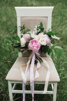 Bruidsboeket met crème rozen en roze pioenrozen staat op een stoel