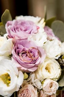 Bruidsboeket met paarse en witte bloemen en ringen