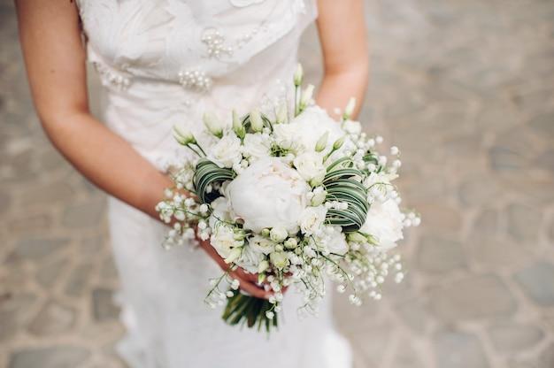 Bruidsboeket met pioenrozen in de handen van de bruid onder de sluier.