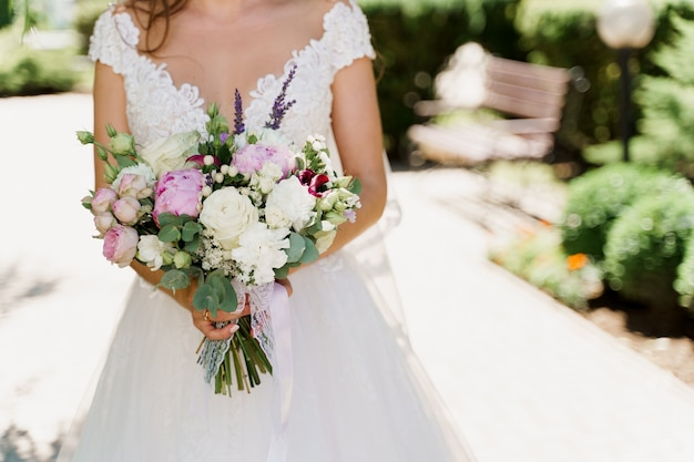 Bruidsboeket met witte rozen, pioenrozen en groene bladeren. bruid in jurk houdt boeket.