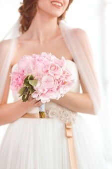 Bruidsboeket mooie roze huwelijksbloemen in handen van de bruid