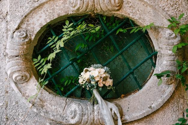 Bruidsboeket op een ovaal raam van een oud huis