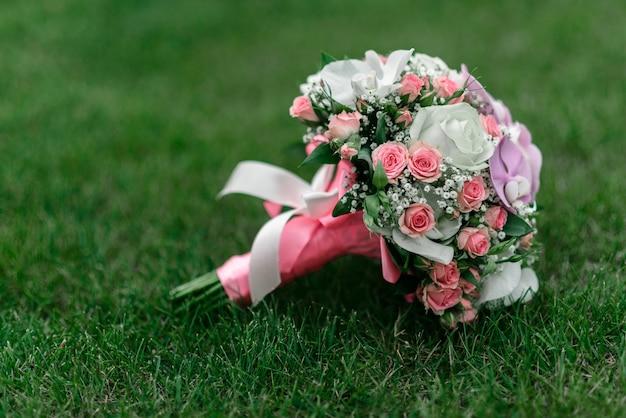 Bruidsboeket op het gras, met rozen, orchideeën en linten