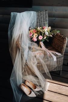 Bruidsboeket, sluier en schoenen van de bruid staan op een stoel.