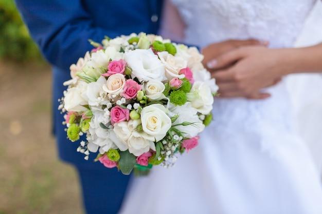 Bruidsboeket van bloemen, waaronder rode hypericum, rozen, lelietje-van-dalen, mini-rozen, geoogste eucalyptus, astilbe, scabiosa, pieris en klimop