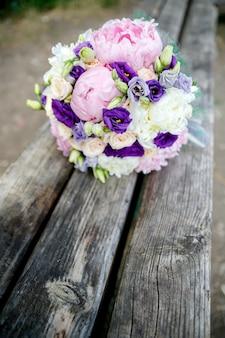 Bruidsboeket van bruiden van pioenrozen en roos op houten achtergrond