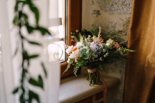 Bruidsboeket van crème rozen roze pioenrozen eustoma waxflower astilbe limonium takken van eucalyptus