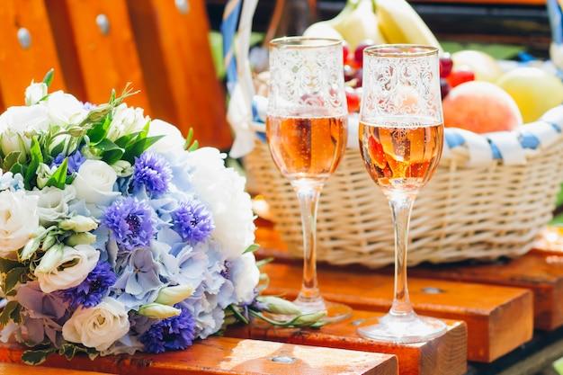 Bruidsboeket van de bruid, twee glazen champagne en een frui