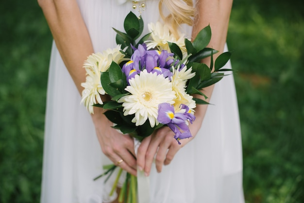 Bruidsboeket van lila paarse irissen en lichtgele gerbera's met takken van groene bladeren