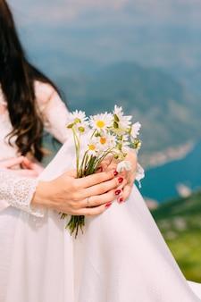 Bruidsboeket van madeliefjes in de handen van de bruid bruiloft in