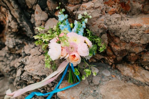 Bruidsboeket van pioenrozen op de rotsen bij de zee bruiloft