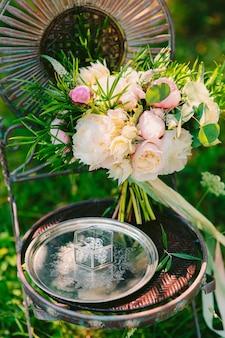 Bruidsboeket van pioenrozen op een vintage metalen stoel bruiloft in m