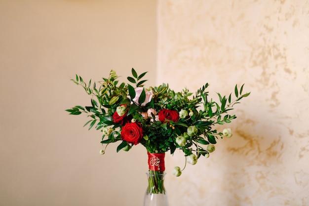 Bruidsboeket van rode en roze rozen buxus takken niet bloeiende knoppen van witte bloemen en rood