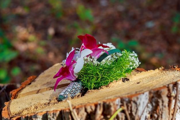 Bruidsboeket van roze pioenrozen, witte hortensia en lichtblauwe bloemen met lichtblauwe linten en huwelijksaccessoires: bruidsarmband en parelhaarclip en boutonnière voor de bruidegom