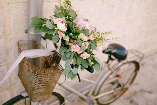 Bruidsboeket van roze rozen takken van eucalyptusboom capsella en witte linten op de fiets