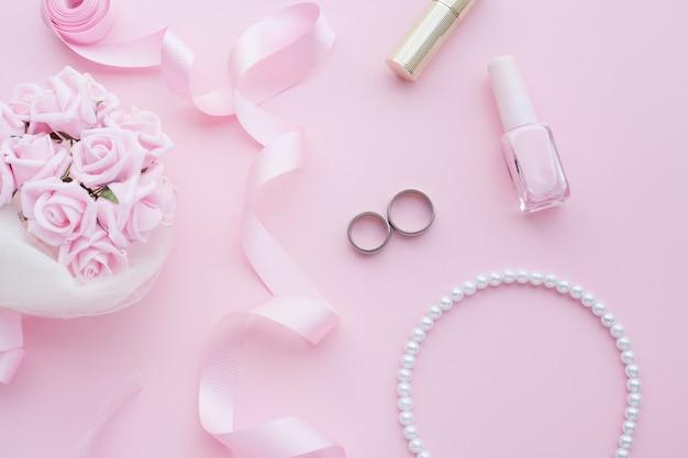 Bruidsboeket van roze rozen, trouwringen, ketting, nagellak en roze lint