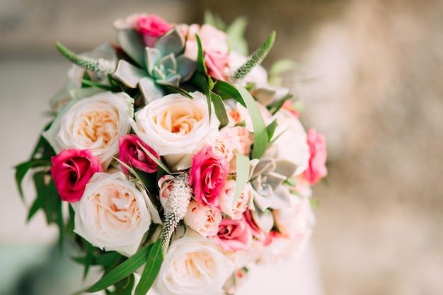 Bruidsboeket van rozen pioenrozen en vetplanten op de rotsen w