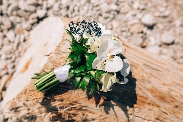 Bruidsboeket van witte calla lelies en blauwe mahonia liggend op de boom