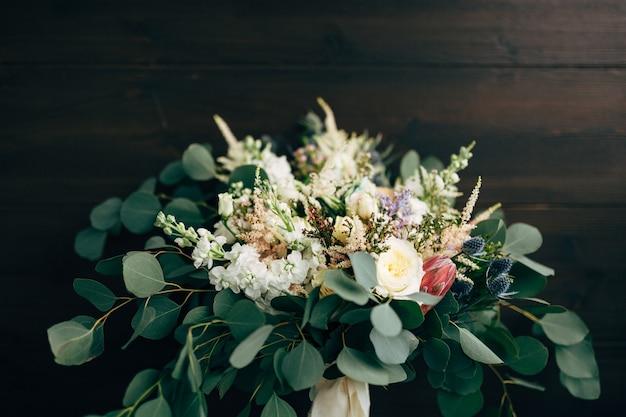 Bruidsboeket van witte en crèmekleurige rozentakken van eucalyptusboom protea eryngium en delphinium