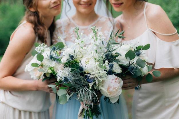 Bruidsboeketten in de handen van de bruid en bruidsmeisjes