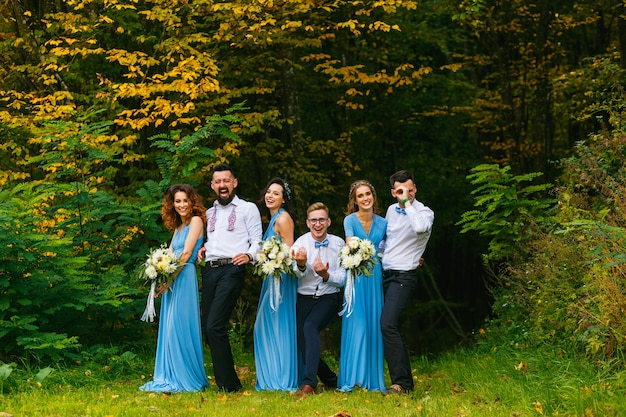 Bruidsjonkers en bruidsmeisjes hebben plezier tijdens de huwelijksceremonie