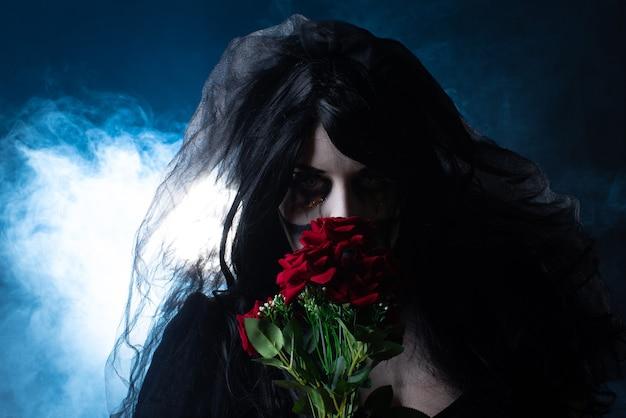 Bruidskadaver met zwarte sluier en boeket rode rozen in een rokerige omgeving, blauwachtige achtergrond, low key portret, selectieve focus.