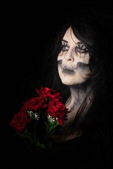 Bruidskadaver met zwarte sluier met een boeket rode rozen, zwarte achtergrond, low key portret, selectieve focus.