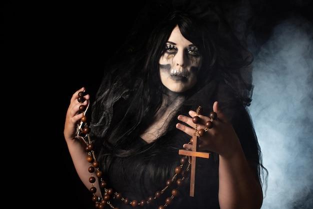 Bruidskadaver met zwarte sluier met een grote rozenkrans zwarte achtergrond, low key portret, selectieve focus.