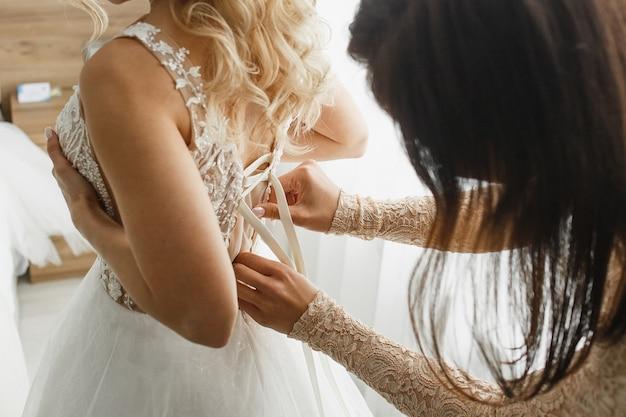 Bruidsmeisje bindt een kanten trouwjurk aan de bruid