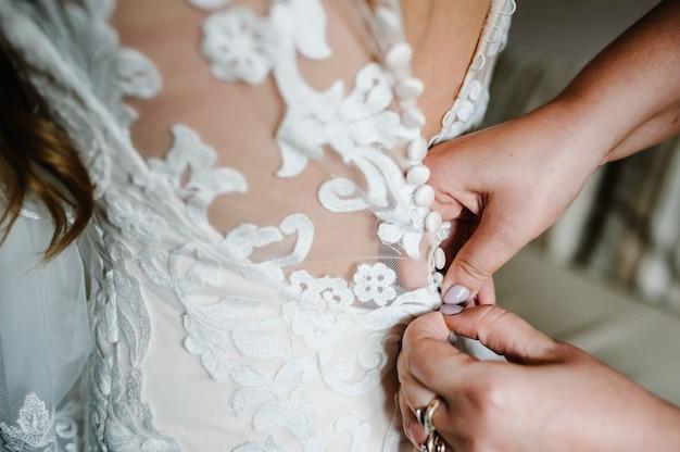 Bruidsmeisje dat bruid helpt knopen op korset vast te maken en haar kleding te krijgen