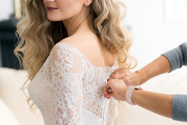 Bruidsmeisje dichtknopen trouwjurk aan bruid