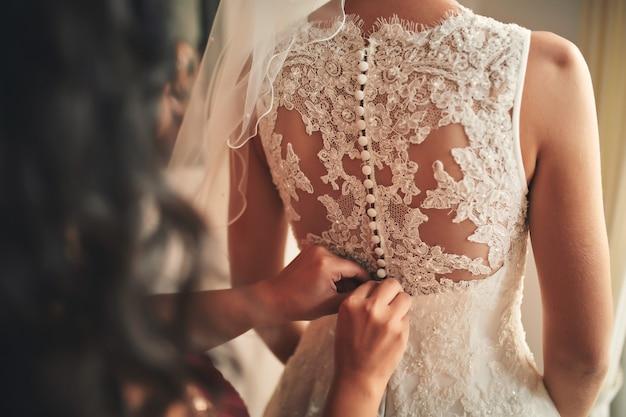 Bruidsmeisje die bruid helpen korsetclose-up vastmaken. trouwdag.