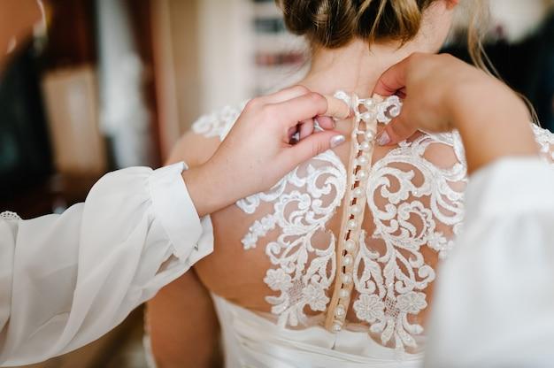 Bruidsmeisje helpt bruid vastknopen op korset en krijgt haar jurk, bruid in de ochtend voorbereiden op de huwelijksdag.