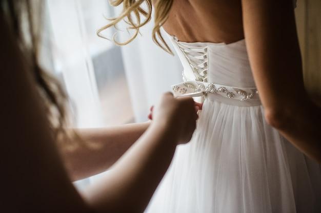 Bruidsmeisje helpt om een trouwjurk te dragen