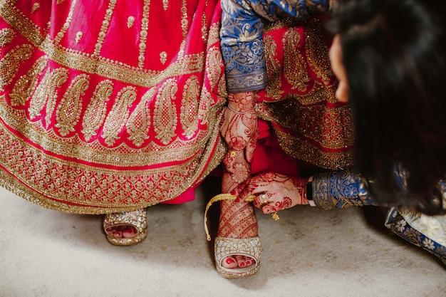 Bruidsmeisje helpt om schoenen indiase bruid te dragen