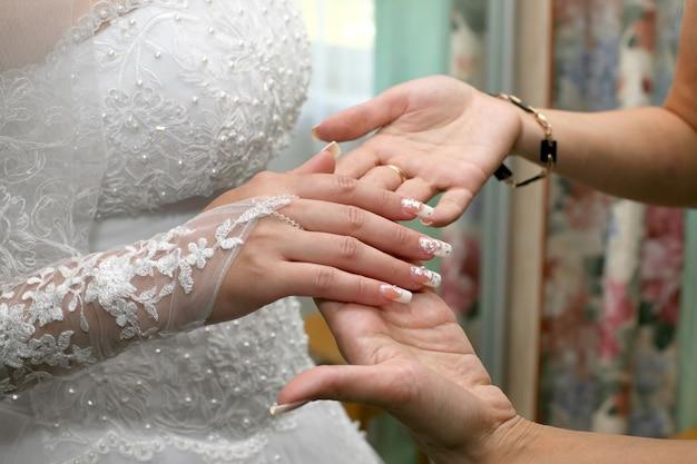 Bruidsmeisje inspecteert de manicure van de bruid