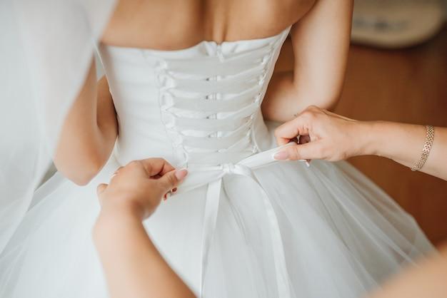 Bruidsmeisje maakt boog-knoop op de achterkant van bruiden trouwjurk
