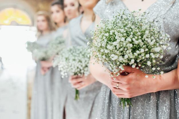 Bruidsmeisjes die bloemen in hun handen houden